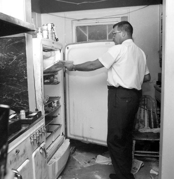 An investigator examining the icebox where the bodies were found.